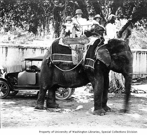 John Dutton Wright, his wife Ysabel Wright, and their children John Jr. and Anna seated on an elephant, with a car in the background, ca. 1921