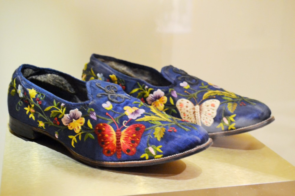 "Floral motives served to enliven the grey environments of urban centers by rooting people back to the natural world. Even men in their off-hours got caught up with the floral trend: these ""Albert"" slippers are hand embodied with pansies and butterflies that are reminiscent of silk moths, the source of silk thread used in the embroidery. Shoes: French, c.1860s Collection of the Bata Shoe Museum)"