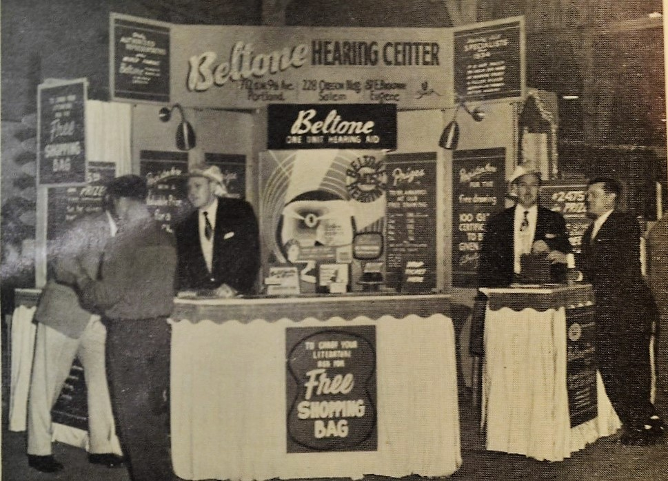 Beltone hearing aid exhibit at the Oregon State Fair, c.1956. The exhibit was designed by Harry L. Marx of Portland to attract and stop people in the aisles. Salesmen were required to wear flashy hats.