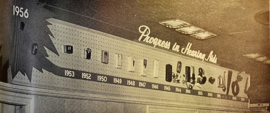 "Inside the above store, with a display of ""Progress in Hearing Aids,"" showing the development and miniaturization of hearing aids since 1890s."